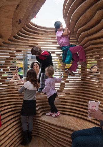 Visitors climb inside a sukkah at Sukkahville 2013 / Sukkahville