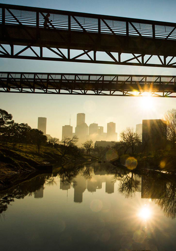 A runner crosses the Rosemont Bridge as the sun rises over downtown in Buffalo Bayou Park in Houston / The Dallas Morning News