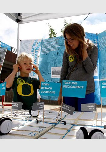 Nels Rogers, 5, listens to the sound of Town Branch with Gena Wirth / Lexington-Herald Ledger